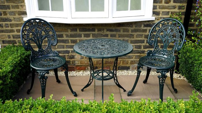 mesas y silla de metal decorando un jardin