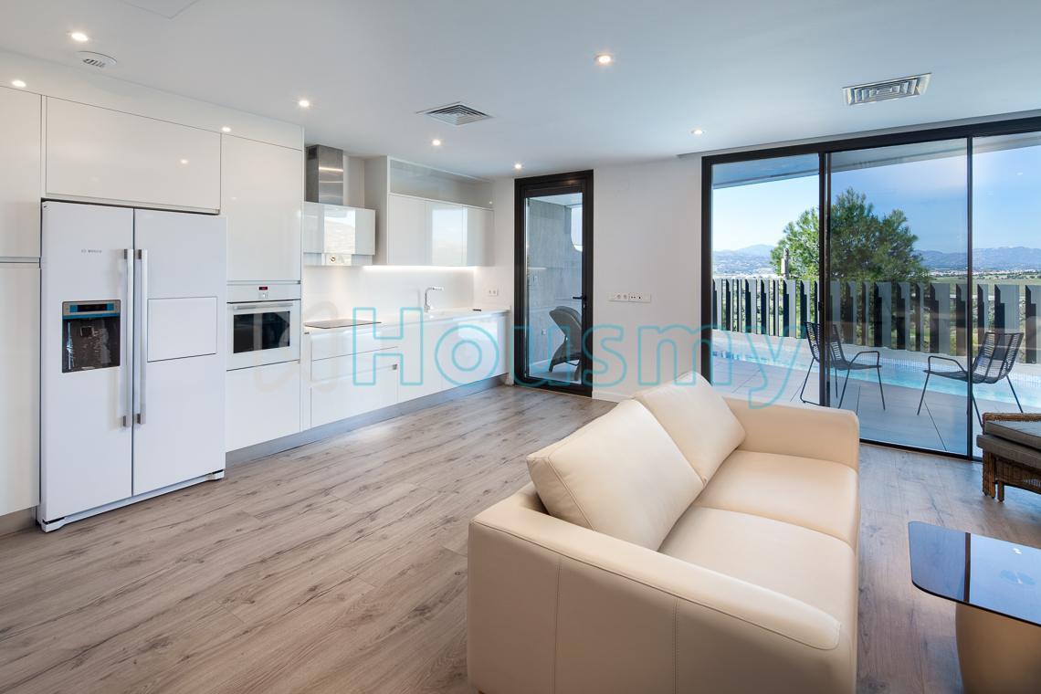 Salón y cocina con acceso a terraza en adosado con piscina en torre del mar. Housmy